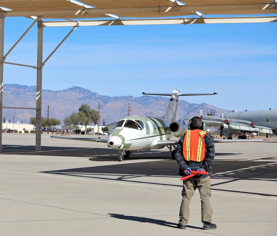 Chad Ellingson, 576th Aerospace Maintenance and Regeneration Squadron, marshals the last T-1A Jayhawk.