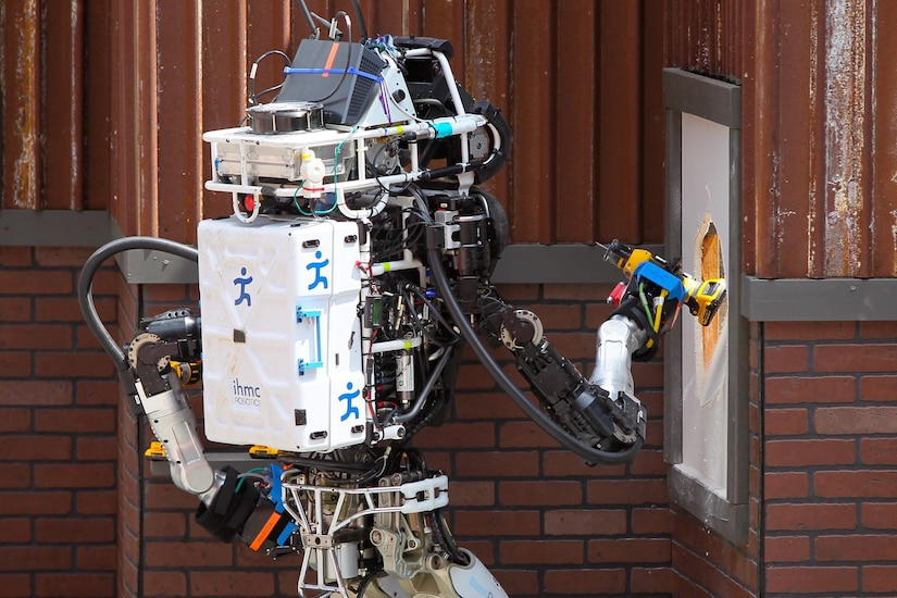 A person-size robot holds a piece of equipment used to cut through drywall on the side of a building.