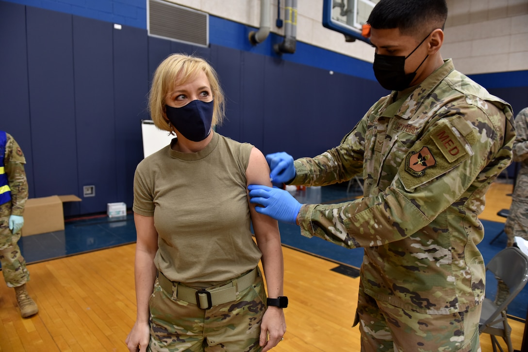 U.S. Air Force Chief Master Sgt. Casy Boomershine, 17th Training Wing command chief, watches as Airman 1st Class Benjamin Loera, 17th Operational Medical Readiness Squadron medical technician for active duty, prepares her arm for the COIVD-19 vaccine at the Mathis Fitness Center on Goodfellow Air Force Base, Texas, Jan. 22, 2021. On Jan. 20, Team Goodfellow vaccinated its frontline and mission essential positions and those who are considered high risk first, in accordance with the Department of the Air Forces distribution plan. (U.S. Air Force photo by Staff Sgt. Seraiah Wolf)