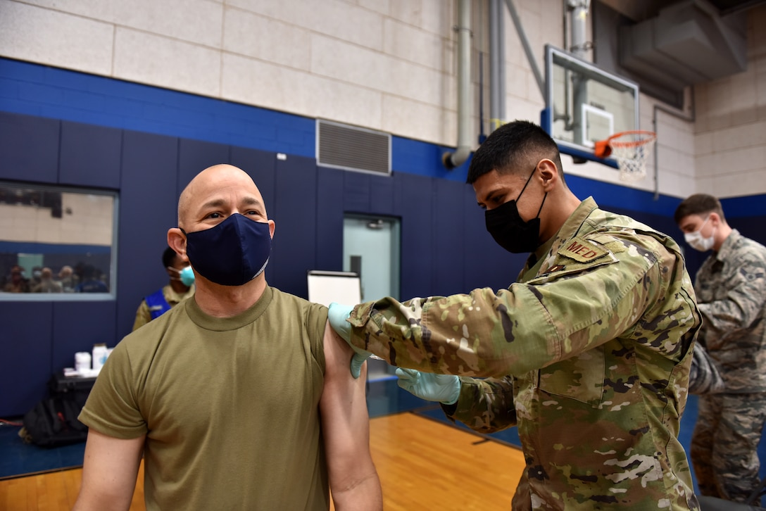 U.S. Air Force Airman 1st Class Benjamin Loera, 17th Operational Medical Readiness Squadron medical technician for active duty, administers the COVID-19 vaccine to Col. Andres Nazario, 17th Training Wing commander at the Mathis Fitness Center on Goodfellow Air Force Base, Texas, Jan. 22, 2021. On Jan. 20, Team Goodfellow vaccinated its frontline and mission essential positions and those who are considered high risk, first, in accordance with the Department of the Air Forces distribution plan. (U.S. Air Force photo by Staff Sgt. Seraiah Wolf)