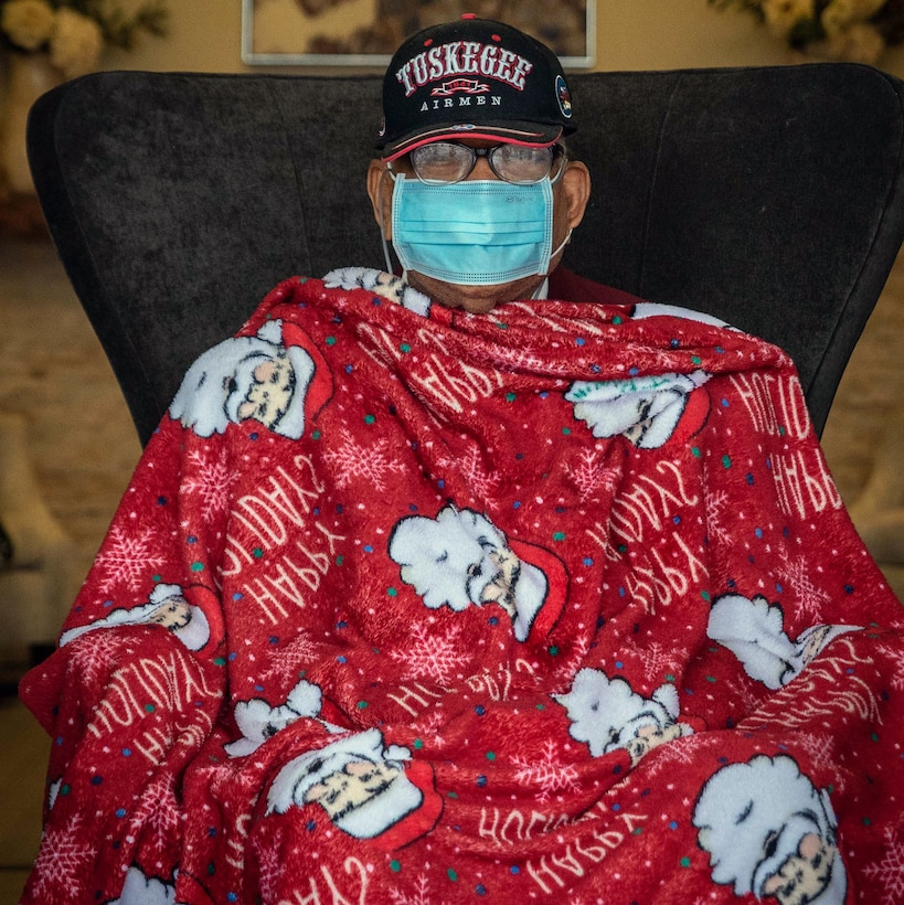 Retired Master Sgt. James Bynum, a documented Original Tuskegee Airman, watches a car parade being held in his honor for his 100th birthday celebration Jan. 9 at the Grandview Assisted Living Facility in San Antonio. To celebrate the milestone, the Tuskegee Airmen San Antonio Chapter held a drive-thru car parade where close to a 100 cars showed up to wish him a happy birthday.