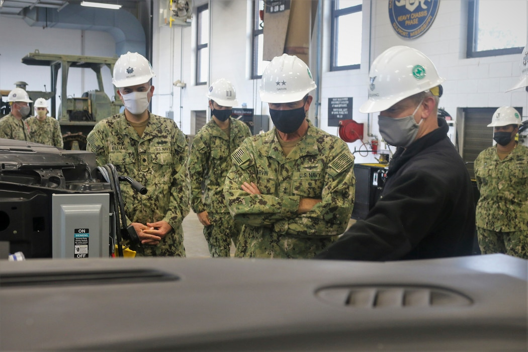 210121-N-N0443-3001 GULFPORT, Miss. (Jan. 21, 2021) Construction Mechanic 1st Class Kyle Dearing, right, talks about how training engines and air compressors are used with Rear Adm. Pete Garvin, commander, Naval Education and Training Command, center, during a tour of the construction mechanic (CM) schoolhouse at Naval Construction Training Center Gulfport.  Students receive hands-on practice working on the type of vehicles employed in Seabee battalions and other commands CMs are assigned to. About 1,700 men and women work as CMs in the Navy, repairing and maintaining heavy construction, tactical and automotive equipment. (U.S. Navy photo by Senior Chief Utilitiesman John D. Meyers)