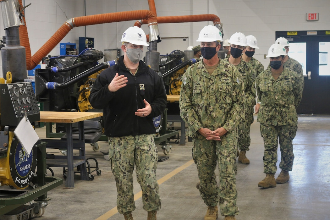 210121-N-N0443-3002 GULFPORT, Miss. (Jan. 21, 2021) Construction Mechanic 1st Class Kyle Dearing, left, discusses the role of the construction mechanic (CM) with Rear Adm. Pete Garvin, commander, Naval Education and Training Command, right.  Seabees learn the skills to repair engines to keep equipment mission ready at the CM schoolhouse at Naval Construction Training Center Gulfport. Students receive hands-on practice working on the type of vehicles employed in Seabee battalions and other commands CMs are assigned to. CMs repair and maintain heavy construction and automotive equipment including, buses, dump trucks, bulldozers, rollers, cranes, backhoes, pile drivers, and tactical vehicles. (U.S. Navy photo by Senior Chief Utilitiesman John D. Meyers)