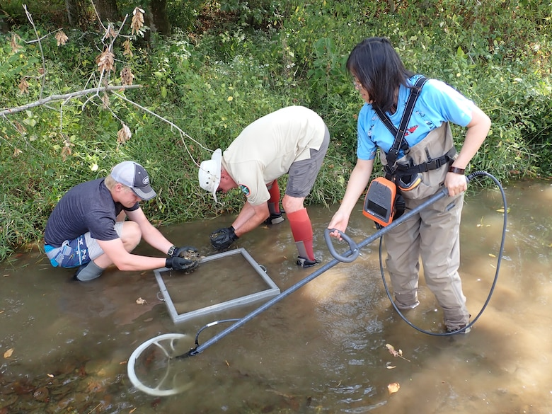 Dan Hua (Right), Tennessee Wildlife Resources Agency wildlife biologist and facility supervisor of the Cumberland River Aquatic Center in Gallatin, Tennessee; uses a device that recognizes tagged mussels, while Don Hubbs (Center), wildlife biologist and mussel recovery coordinator; and Jack Fetters, wildlife technician; sieve substrate to capture tagged mussels Oct. 1, 2019 at Lick Creek in Santa Fe, Tennessee. When the U.S. Army Corps of Engineers Nashville District lowered Lake Cumberland in Kentucky in 2008 to relieve pressure on Wolf Creek Dam, an agreement with the U.S. Fish and Wildlife Service to mitigate environmental impacts resulted in mitigation dollars being committed to the aquatic center. (Photo by Kristin Irwin)
