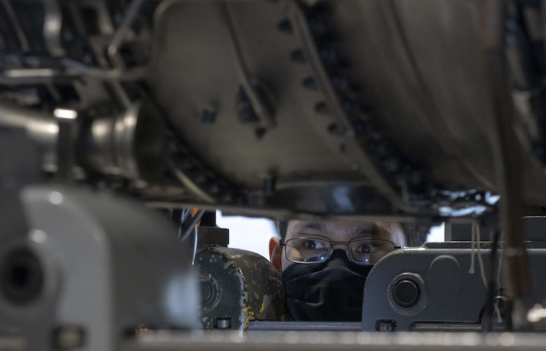 A photo of an Airman looking under an engine.