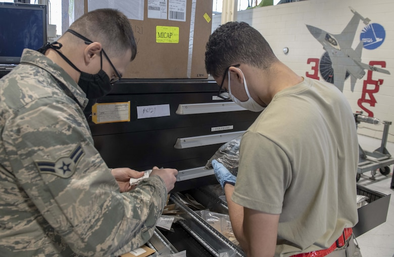 A photo of Airmen looking at parts in a shop.