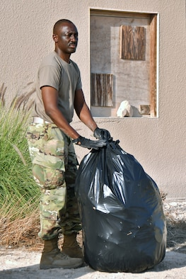 Airman with trash bag.
