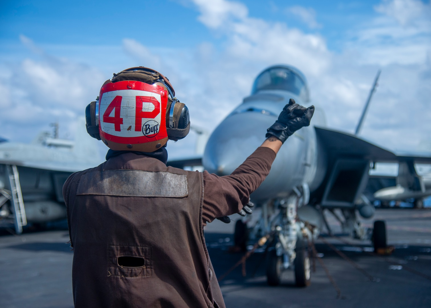 """PACIFIC OCEAN (Jan. 23, 2021) – U.S. Navy Airman John Ramoslayton, from Carolina, Puerto Rico, assigned to the """"Golden Warriors"""" of Strike Fighter Squadron (VFA) 87, directs Rear Adm. Doug Verissimo, commander, Carrier Strike Group Nine, to conduct pre-flight checks on an F/A-18E Super Hornet, assigned to VFA 87, aboard the aircraft carrier USS Theodore Roosevelt (CVN 71) Jan. 23, 2021. The Theodore Roosevelt Carrier Strike Group is on a scheduled deployment to the U.S. 7th Fleet area of operations. As the U.S. Navy's largest forward deployed fleet, with its approximate 50-70 ships and submarines, 140 aircraft, and 20,000 Sailors in the area of operations at any given time, 7th Fleet conducts forward-deployed naval operations in support of U.S. national interests throughout a free and open Indo-Pacific area of operations to foster maritime security, promote stability, and prevent conflict alongside 35 other maritime nations and partners."""
