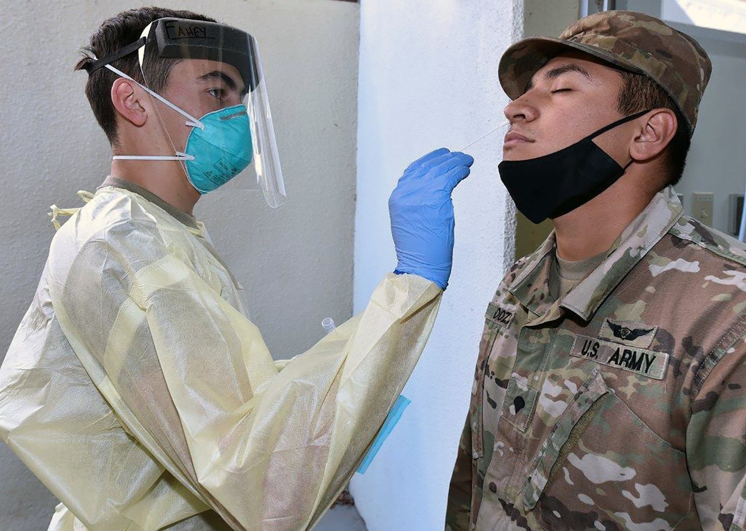 Pvt. Dylan Fahey with Company A, 232nd Medical Battalion, uses a cotton swap to test Spc. Derek Mendoza, assigned to Headquarters Support Company, MEDCoE, for COVID-19.