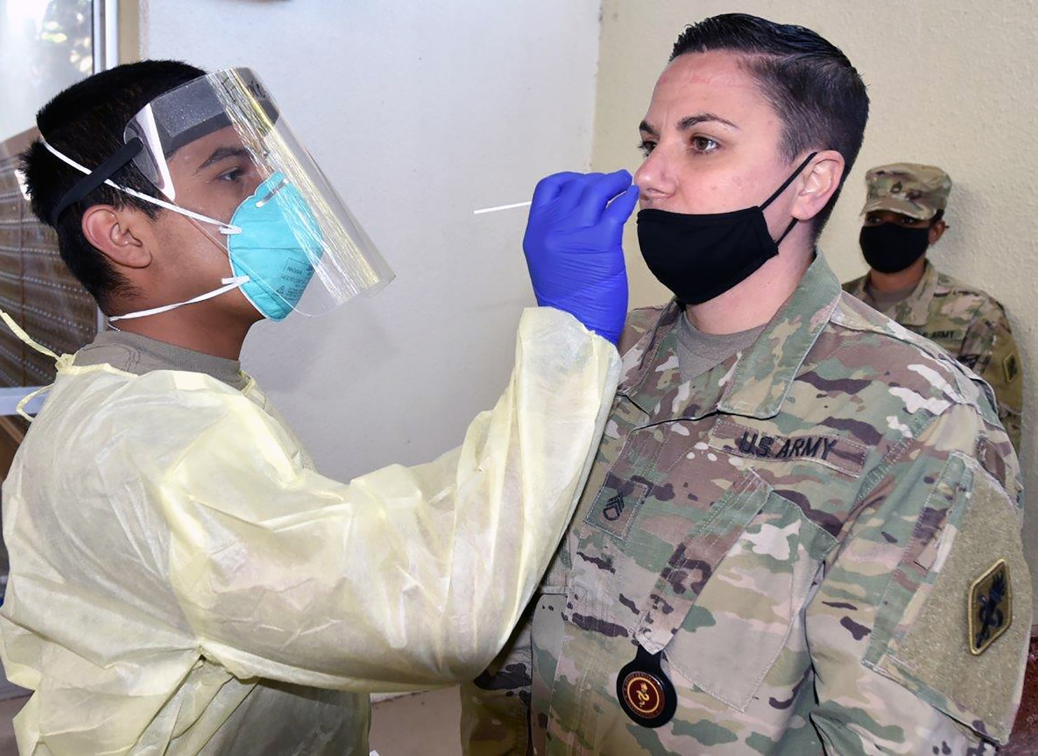 Pvt. Daniel Flores with Company A, 232nd Medical Battalion, uses a cotton swap to test Staff Sgt. Nicole Conti with Company A, 188th Medical Battalion, for COVID-19.