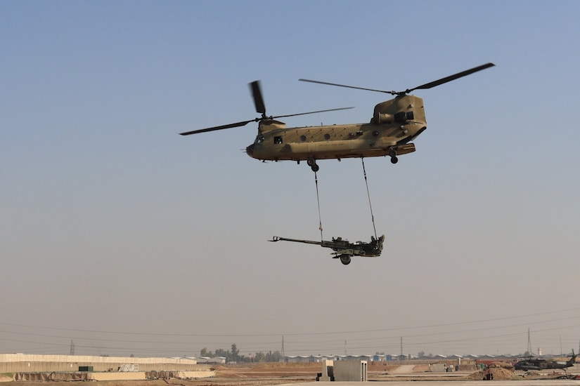 A CH-47 Chinook helicopter operated by Soldiers with Bravo Company, 3-238th General Support Aviation Battalion, 28th Expeditionary Combat Aviation Brigade sling loads an M777 Howitzer during an exercise with Soldiers with the 2-319th Field Artillery Regiment.