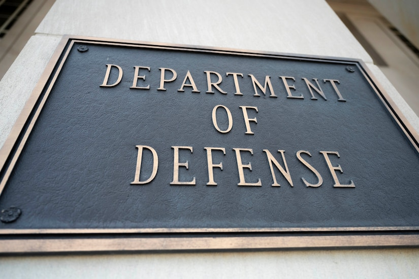"A metal placard reading ""DEPARTMENT OF DEFENSE"" is displayed on a building facade."