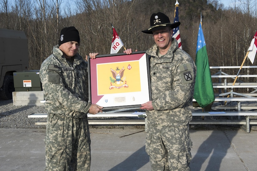 Two guardsmen pose holding a framed picture.
