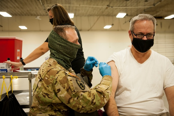 Nebraska National Guard Staff Sgt. Brad Wardyn, a flight medic with Company G, 2-104th General Support Aviation Battalion, administers the COVID-19 vaccine to Tom Kent, the resident and CEO for the Nebraska Public Power District, Jan. 21, 2021, in Columbus, Nebraska.