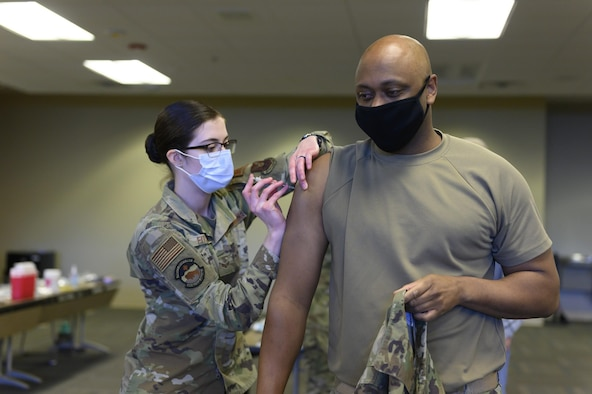 Senior Airman Brittney Fitschen, 28th Health Care Operations Squadron family health technician, administers a COVID-19 vaccine to Lt. Col. David Herndon, 28th Security Forces Squadron commander, at Ellsworth Air Force Base, S.D., Jan. 15, 2021.