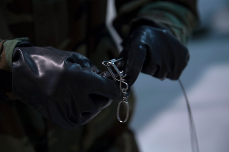 An US Air Force member prepares arming wire while wearing chemical, biological, radiological and nuclear equipment.
