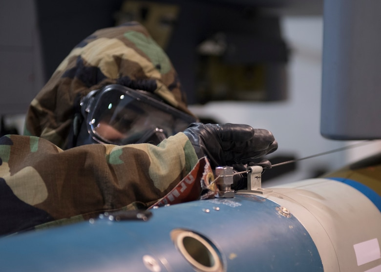 An US Airforce member threads arming wire while wearing chemical, biological, radiological and nuclear equipment.