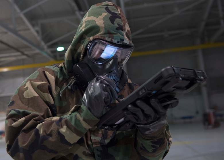 An US Airforce member uses a tablet to check technical order while wearing chemical, biological, radiological and nuclear equipment.