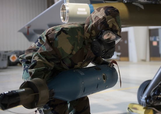 An US Air Force member lifts the guidance potion of a bomb.