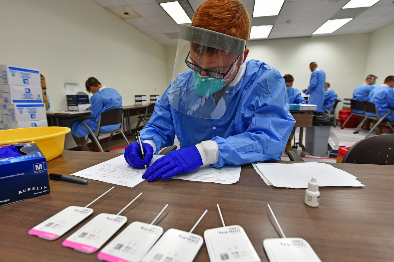 A person wearing personal protective equipment sits at a table and writes on a piece of paper.