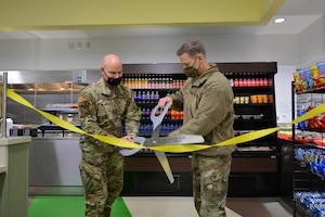 U.S. Air Force Col. David Berkland, the 354th Fighter Wing commander, and Chief Master Sgt. John Lokken, the 354th FW command chief, cut a ribbon during the reopening ceremony of the satellite dining facility (DFAC) on Eielson Air Force Base, Alaska, Jan 21, 2021.