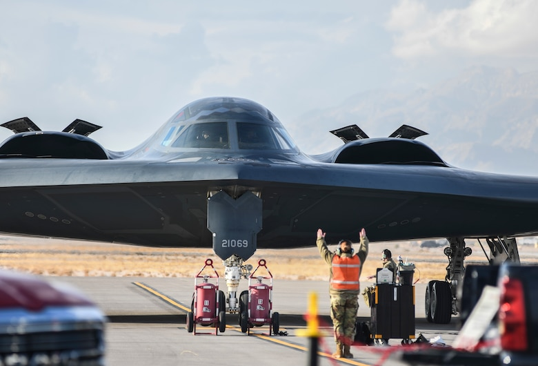 A 393rd Expeditionary Bomb Squadron crew chief guides a B-2 Spirit Stealth Bomber to a parking place during Red Flag 21-1, at Nellis Air Force Base, Nevada, Jan. 22, 2021. Well-trained Airmen are an important component to readiness and RF 21-1 prepare Airmen for future threats through experience in realistic combat scenarios. (U.S. Air Force photo by Staff Sgt. Sadie Colbert)