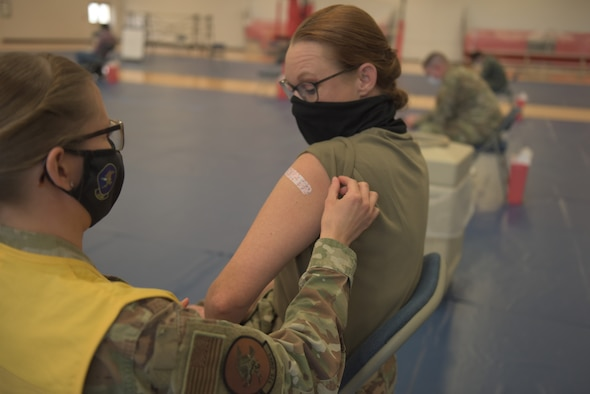 U.S. Air Force Tech. Sgt. Haley Lecomte, 325th Operational Medical Readiness Squadron technician, left, applies a bandage to Chief Master Sgt. Kati Grabham, 325th Fighter Wing command chief, right, after administering the COVID-19 vaccine at Tyndall Air Force Base, Florida, Jan. 21, 2021. The vaccine was initially distributed by the U.S. Food and Drug Administration and is covered by the military healthcare system. (U.S. Air Force photo by Staff Sgt. Magen M. Reeves)
