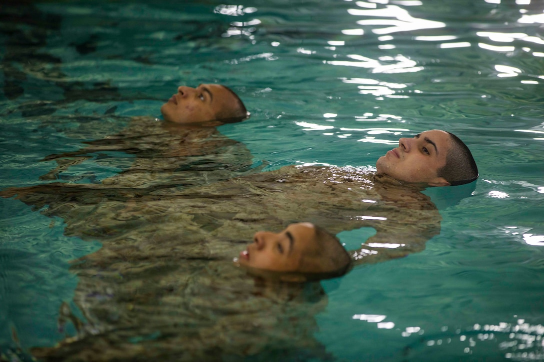 Three Marine Corps recruits float on their backs in a pool.