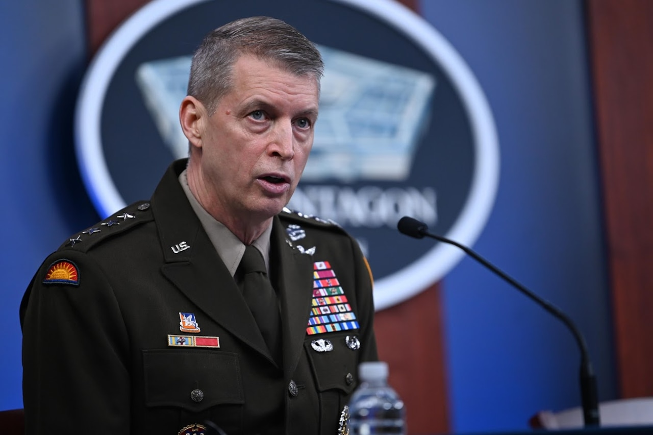 Man in military uniform speaks into a microphone. A sign indicating that he is at the Pentagon is in the background.