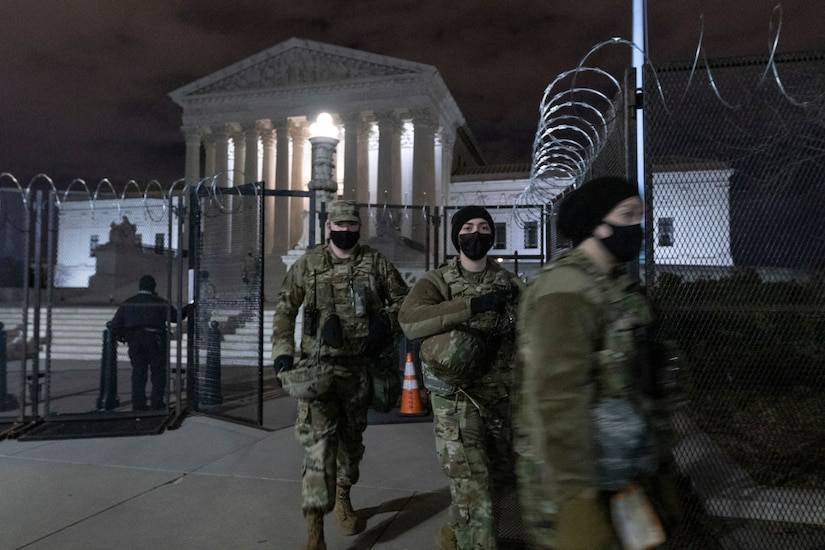 Guardsmen in front of the Supreme Court building on Capitol Hill make their way outside of the perimeter fencing.