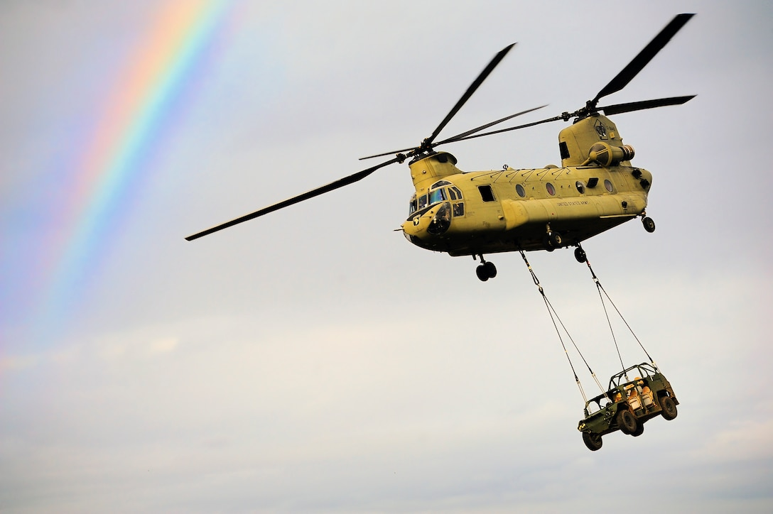 A helicopter flies next to a rainbow while carrying a vehicle.