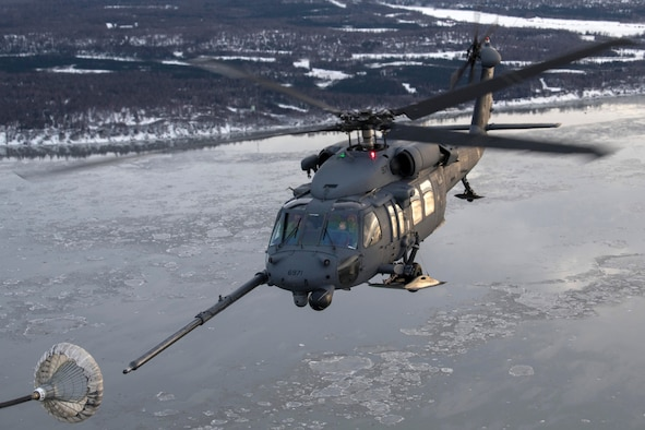 U.S Air Force HH-60 Pave Hawk helicopter assigned to the 210th Rescue Squadron, Alaska Air National Guard, conducts aerial refueling from a U.S. Air Force HC-130J Combat King II assigned to the 211th Rescue Squadron, Alaska Air National Guard, over Alaska, Jan. 21, 2021, during Operation Noble Defender