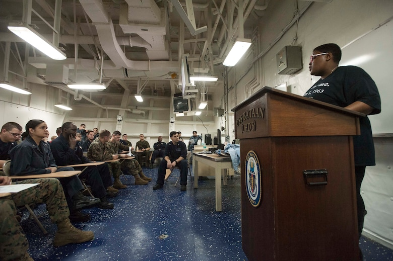 Service members aboard ship attend a training session.