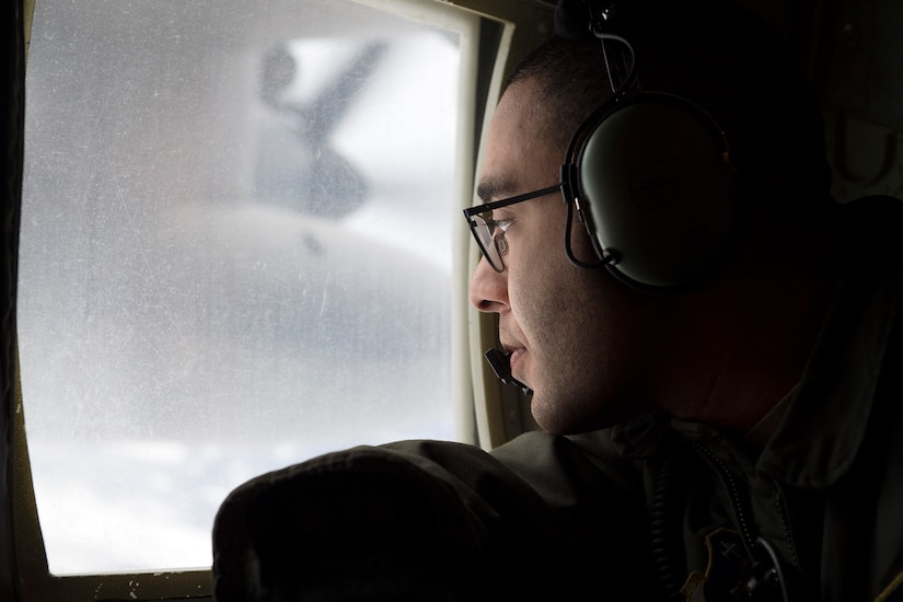U.S. Air Force Senior Airman Marcus Moloney, a loadmaster assigned to the 211th Rescue Squadron, Alaska Air National Guard, looks for a simulated search-and-rescue target over Alaska, Jan. 21, 2021, during Operation Noble Defender. Operation Noble Defender is a North American Air Defense Command air-defense operation which allows dynamic training for operational readiness in an arctic environment.