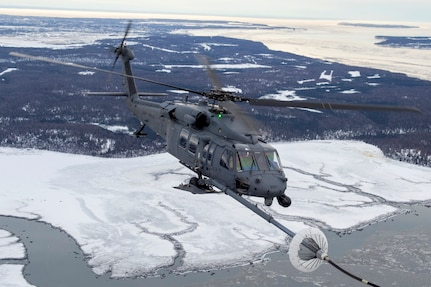 A U.S Air Force HH-60G Pave Hawk helicopter assigned to the 210th Rescue Squadron, Alaska Air National Guard, conducts aerial refueling from a U.S. Air Force HC-130J Combat King II assigned to the 211th Rescue Squadron, Alaska Air National Guard, over Alaska, Jan. 21, 2021, during Operation Noble Defender. Operation Noble Defender is a North American Air Defense Command air-defense operation which allows dynamic training for operational readiness in an arctic environment.
