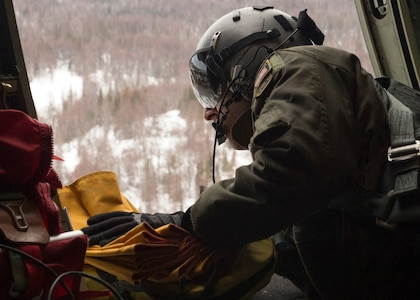 U.S. Air Force Senior Airman Marcus Moloney, a loadmaster assigned to the 211th Rescue Squadron, Alaska Air National Guard, drops a freefall bundle of supplies to a simulated victim during a search and rescue exercise over Alaska, Jan. 21, 2021, as part of Operation Noble Defender. Operation Noble Defender is a North American Air Defense Command air-defense operation which allows dynamic training for operational readiness in an arctic environment.