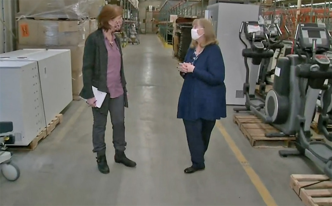 Two women chat in a warehouse.