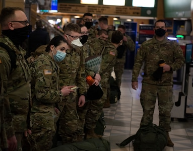 Soldiers with the Vermont National Guard's 172nd Law Enforcement Detachment wait to check their bags at Burlington International Airport in South Burlington, Vermont, Jan. 26, 2021. The Soldiers will deploy to the U.S. European Command area of responsibility to support Operation Freedom's Sentinel. (U.S. Army National Guard photo by Don Branum)