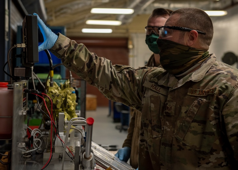 Staff Sgt. Steven Hall, 4th Component Maintenance Squadron centralized repair facility expeditor (front), and Tech. Sgt. Jeremy Fannin, 4 CMS centralized repair facility NCO in charge (back), prepare to test a stabilator actuator at Seymour Johnson Air Force Base, North Carolina, Jan. 7, 2021.