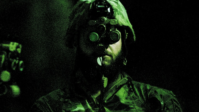 A soldier looks at the camera while wearing night vision goggles.