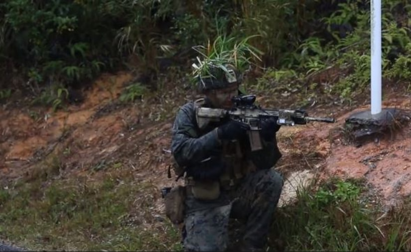 Video screen grab shows a Marine crouched in the jungle holding a rifle.