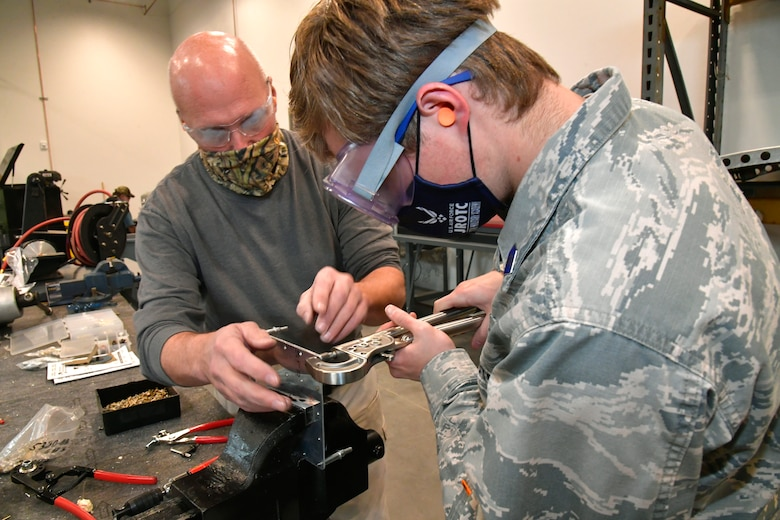 Darrel Gronau (left), aviation structure repair instructor, teaches Connor Innocenzi, Utah Military Academy student, proper riveting technique on part of an aircraft fuselage skin.