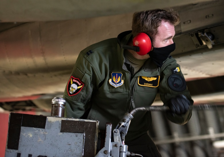U.S. Air Force Capt. Cameron Emerson, 493rd Fighter Squadron F-15C Eagle pilot, assists with pre-flight maintenance at Royal Air Force Lakenheath, England, Jan. 21, 2021. The 48th Fighter Wing is dedicated to developing a force of multi-capable Airmen to drive the mission more effectively through the integration of Agile Combat Employment concepts. (U.S. Air Force photo by Airman 1st Class Jessi Monte)