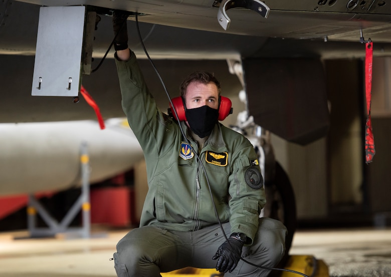 U.S. Air Force Capt. Cameron Emerson, 493rd Fighter Squadron F-15C Eagle pilot, assists with pre-flight checks at Royal Air Force Lakenheath, England, Jan. 21, 2021. The 48th Fighter Wing is dedicated to developing a force of multi-capable Airmen to drive the mission more effectively through the integration of Agile Combat Employment concepts. (U.S. Air Force photo by Airman 1st Class Jessi Monte)
