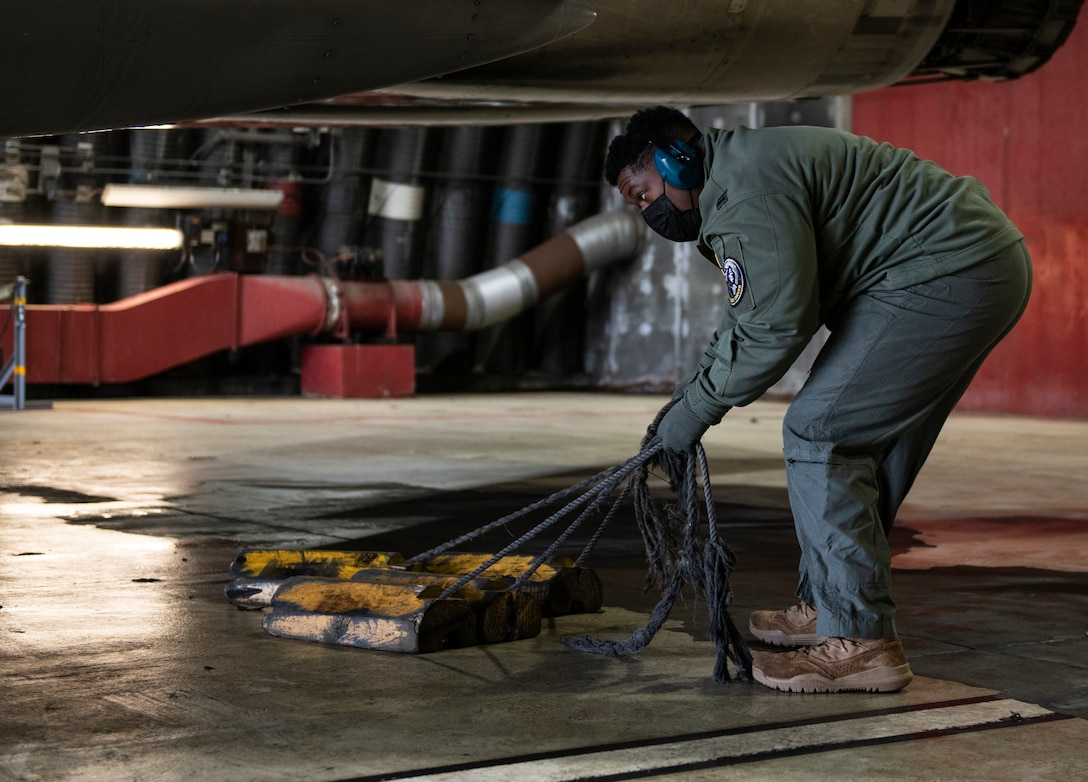 U.S. Air Force Capt. Joshua Jones, 493rd Fighter Squadron F-15C Eagle pilot, removes chocks from an aircraft prior to take-off at Royal Air Force Lakenheath, England, Jan. 21, 2021. Aircrew and other Airmen and Aircrew from non-maintenance career fields recently had the opportunity to practice Agile Combat Employment concepts while helping generate sorties for the 493rd FS. (U.S. Air Force photo by Airman 1st Class Jessi Monte)