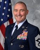 photo of man in front of flag in uniform