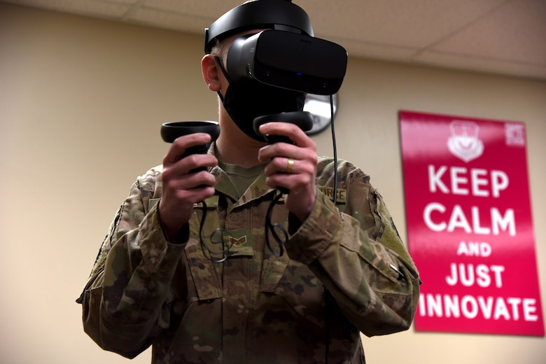 An Airmen holds joysticks and uses a virtual reality headset to test contacting software inside of the Innovation Lab.
