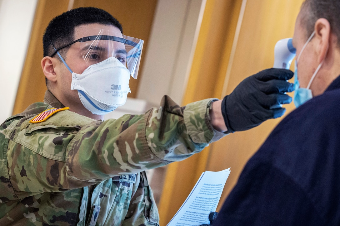 A soldier wearing a face mask and gloves takes the temperature of a patient.