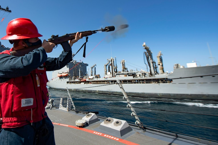 A sailor fires a shot from a ship to another ship at sea.
