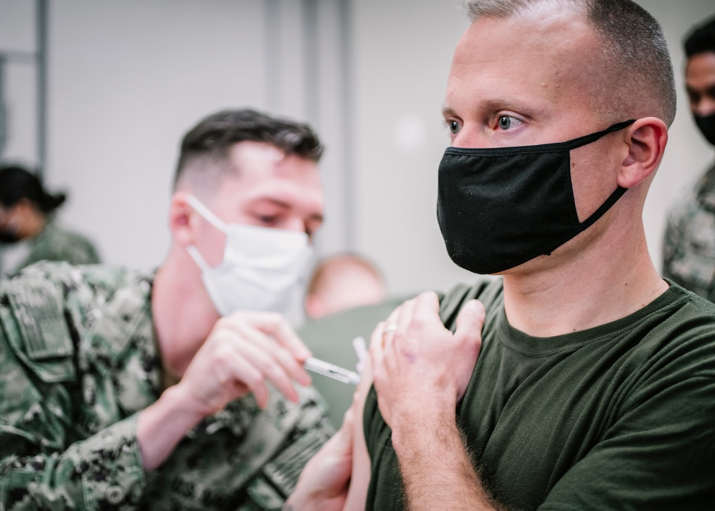 U.S. Marine Corps Col. James Lively, right, the commanding officer of the 11th Marine Expeditionary Unit (MEU), receives the Pfizer-BioNTech COVID-19 vaccine at Naval Hospital Camp Pendleton, California, Jan. 11, 2021. The 11th MEU is one of the first units with I Marine Expeditionary Force to be allocated the vaccine due to its upcoming deployment. The vaccine was authorized for emergency use by the U.S. Food and Drug Administration and is voluntary to receive. (U.S. Marine Corps photo by Staff Sgt. Donald Holbert)
